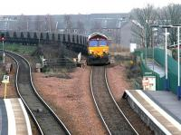 Coal empties from Longannet power station approaching Camelon, westbound, on 10 December 2004. The locomotive is crossing the bridge over the A9 alongside the overgrown island platform of the original Camelon station, with the old stairway between platform and road level still visible [see image 13253]. <br><br>[John Furnevel 10/12/2004]