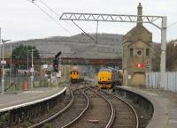 <I>Class 37 convention</I>. As 37401 on a passenger service departs from Carnforth for Barrow, 37423 arrives from Settle Junction with an RHTT working on 3rd November 2017, substituting for the usual Class 66 power. 37422 was the rear loco and a further Class 37 can be seen stabled in the West Coast yard on the left. <br><br>[Mark Bartlett 03/11/2017]