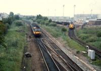 477 E&G train heads for Glasgow past a 37 oil train leaving the Bishopbriggs oil terminal.<br><br>[Ewan Crawford //1987]