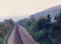 Looking South from the road overbridge in 1987, the remains of a platform at Llanvihangel can be seen on the right. The narrow gauge trackbed to the right of the green fence in the background is the long closed Grwyne Fawr Reservoir Railway; which like many such railways, was built to serve reservoir construction; and abandoned once its role was complete. (thanks to John Thorn for confirming this). This location is now very overgrown, but the shallow embankment in the field to the South of this view is probably still there.<br><br>[Ken Strachan /04/1987]
