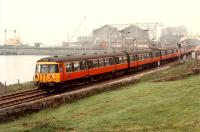 Eastbound 303 passing Bowling Harbour. Arnott Youngs yard is in the background. <br><br>[Ewan Crawford //1990]